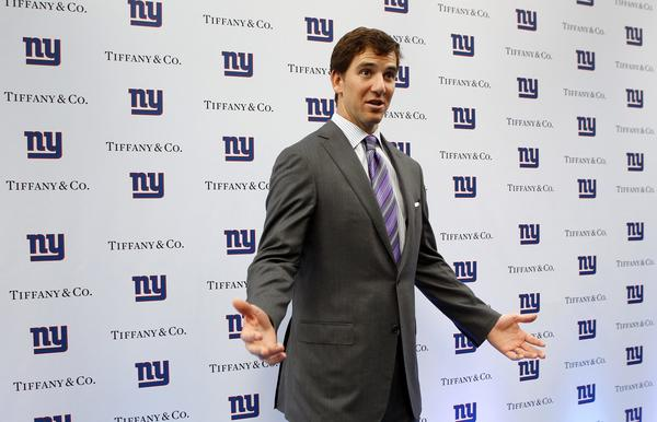 Giants quarterback Eli Manning gestures toward the media as he arrives at Tiffany & Co.'s flagship store to be presented with his newly designed ring commemorating their Super Bowl victory earlier this year in New York,