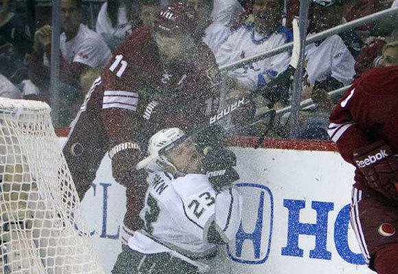 The Kings' Dustin Brown gets slammed into the boards by Phoenix's Martin Hanzal.