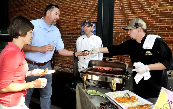 Jessica and Corey Green of Greencastle, Pa., get blackened fish tacos from Jeremiah Twigg, right, as Chef John James looks on at Bulls & Bears during the Taste of the Arts.