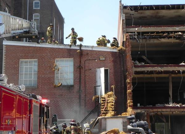 Firefighters toss hay off of the of the two-story addition to the commissioners' office at 14 N. Main St.