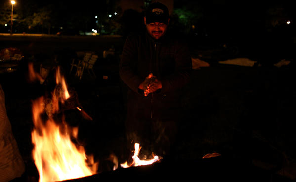 Richard Del Rio, with the Mental Health Movement warms himself by the fire outside of the Woodlawn Mental Health Clinic.