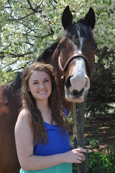 Emily Love of Petoskey poses with her horse Dane. Love will be moving to France this summer to train with equestrian champion Benjamin Aillaud.