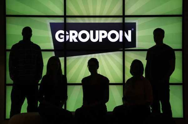 Employees at Groupon Inc. pose with the company logo. A Wall Street Journal report says regulators may be probing a pre-earnings Groupon stock surge.