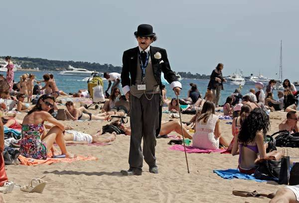 A man dressed as Charlie Chaplin walks on the beach in Cannes during the 65th Cannes Film Festival.