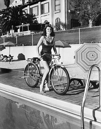 Circa 1940: Rita Hayworth poses poolside on a bicycle.