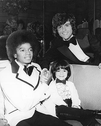 February 1974: Singers Michael Jackson, left, and Donny Osmond clasp hands while posing with child actor Ricky Segall, center, at the American Music Awards.