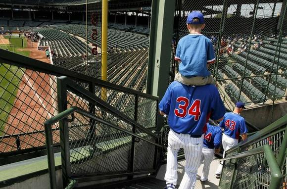 After a trip to the scoreboard, Kerry Wood and his son Justin head back to the field. ¿ Phil Velasquez, Chicago Tribune, May 18, 2012