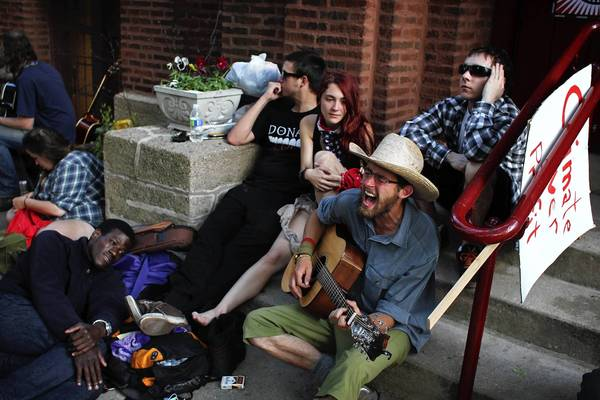 Peter Diebold, 23, right, of Glenn Ellyn, sings and plays the guitar while sitting other Occupy Protesters outside of Wellington Avenue United Church of Christ.