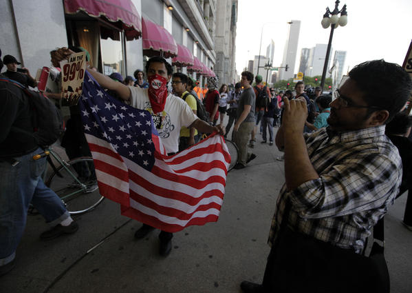 An anti-NATO protester from New York City joins with workers on strike outside the Congress Hotel in downtown Chicago Friday evening.