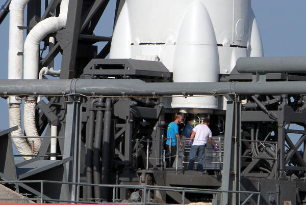 SpaceXworkers gather near the engines of a Falcon 9 rocket after a launch attempt was aborted.