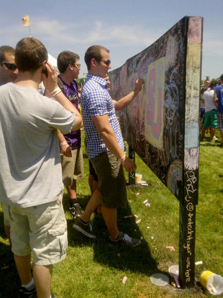 Preakness attendees write on a chalkboard in the center of the Preakness 2012 infield.