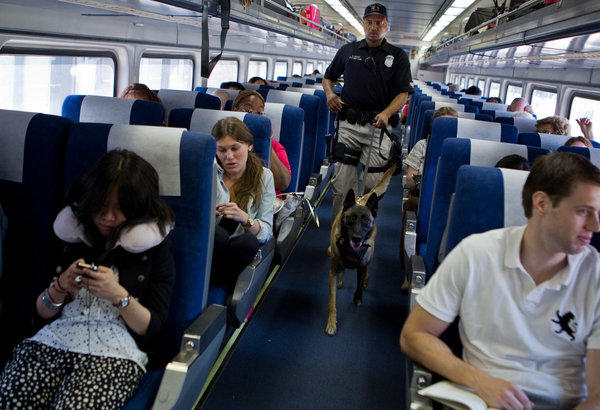 "Amtrak police officer Stan Bailey from Chicago with dog ""Riot"" boards Amtrak train ""Saluki"" at Homewood station Saturday. (Zbigniew Bzdak/Chicago Tribune)"