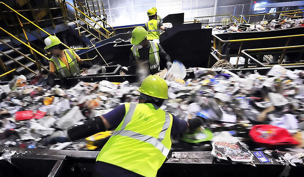 A river of recyclables to be sorted flow past sorters at Waste Management recycling facility near Elkridge, Md.