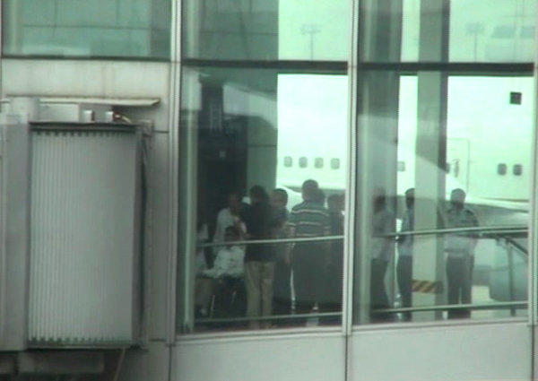 Blind Chinese activist Chen Guangcheng, left, is seen pushed in a wheelchair from an elevator to a sky bridge that is connected to a plane at Beijing International airport.