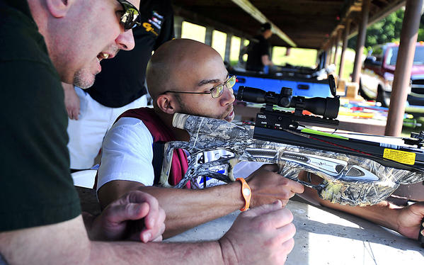 U.S. Army veteran Quadiir Mattox, right, of Atlantic City, N.J. learns to shoot a cross bow with the help of Tom Forman, left, president of the Izaak Walton league during an event for veterans at the Izaak Walton League in Clear Spring Saturday.