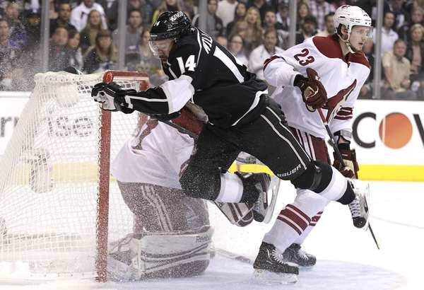 Kings center Colin Fraser stumbles out of the crease as Coyotes defenseman Oliver Ekman-Larsson and goalie Mike Smith concentrate on the puck in the first period in Game 4 on Sunday afternoon at Staples Center.