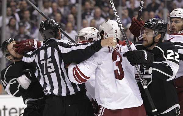 Kings and Coyotes players are separated by a referee during an altercation in front of a goal in the first period of Game 4 on Sunday afternoon at Staples Center.