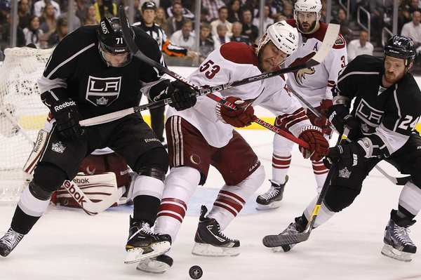 Kings center Jordan Nolan, left, and Coyotes defenseman Derek Morris (53) battle for the puck late in Game 4 at Staples Center on Sunday afternoon