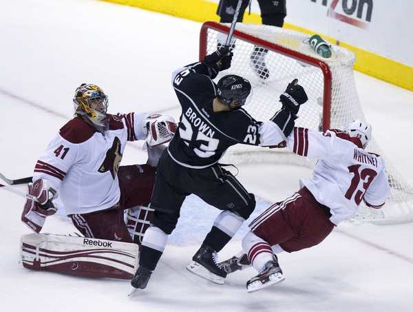 Kings Dustin Brown (23) loses his balance atacking the goal against Coyotes goalie Mike Smith and winger Ray Whitney during Game 4 of the Western Conference finals at Staples Center.