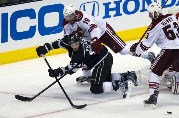Kings center Colin Fraser (24) is knocked off balance by Coyotes winger Shane Doan in Game 4 on Sunday afternoon at Staples Center.