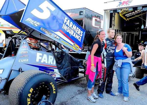 Race car driver Kasey Kahne poses for photos with Hagerstown residents Shannon Sisk, left, and Tania Price Sunday evening prior to the World of Outlaws Sprint Car Series race at Hagerstown Speedway.