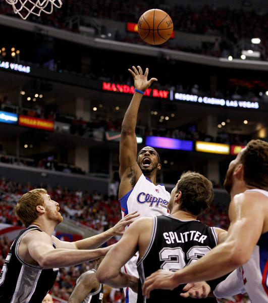 Clippers guard Chris Paul shoots a floater over the Spurs Tiago Splitter and Matt Bonner.
