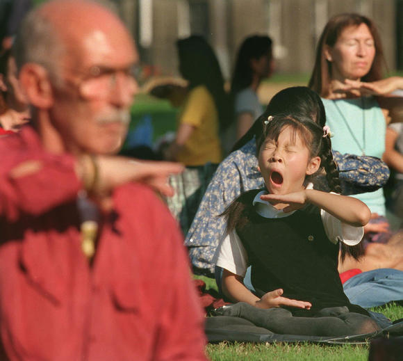 A young Falungong follower yawns during the early morning exercises