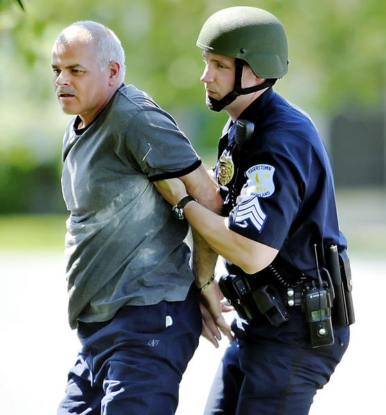 Neil LaPine is led to a police cruiser by Hagerstown City Police Sgt. John Lehman after he barricaded himself inside a Little Hayden Circle home on Friday.