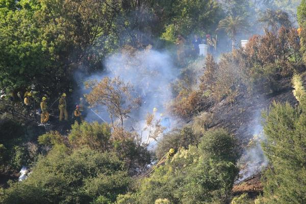 Los Angeles County Fire Department crews battle a small brush fire near the La Canada Flintridge Country Club on Sunday, May 20.