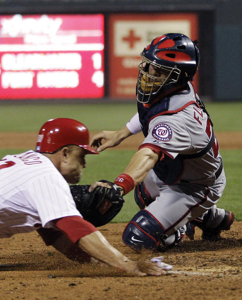 Washington catcher Jesus Flores, right, tags out Philadelphia's Placido Polanco at home as he tries to score on Carlos Ruiz's sixth-inning grounder on Monday in the Nats' 2-1 victory. in the sixth inning of a baseball game, Monday, May 21, 2012, in Philadelphia.