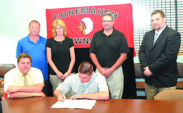 Conemaugh Township head boys basketball coach Chuck Lesko, left, sits next to senior Grant Speigle, who signs a letter of intent to play basketball at Penn Highlands Community College on Monday. They are joined by, standing, from left, stepfather Rich Louder and mother Lori Louder, father Dwight Speigle and Penn Highlands head men's basketball coach Landon Loya.