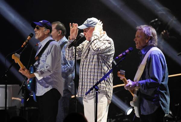 Lead singer Mike Love adjusts his cap during a Beach Boys song on Monday night.