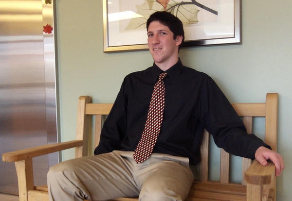 Kevin Becker sits on a bench he donated to one of the hospital's lodging centers, the Hackerman-Patz House.