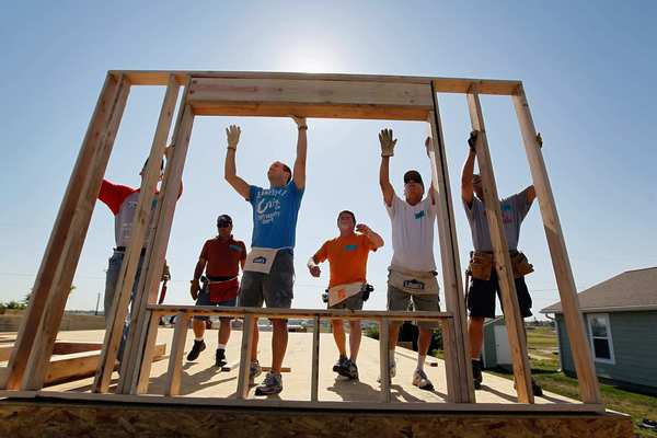 A wall is raised on a Habitat for Humanity house in Joplin, Mo., being built to replace one that was destroyed a year ago after the town was hit by a catastrophic tornado.