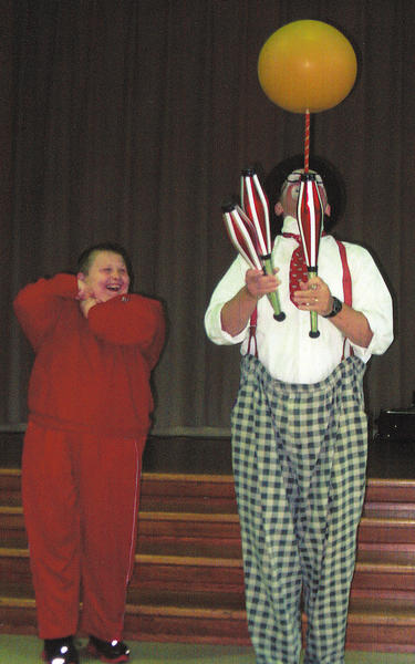 Robert Howell, left, watches Kevin the Clown perform his juggling act while balancing a ball at the same time at the recent variety show put on by Tri-State Civitan Club at the Potomac Center in Hagerstown.