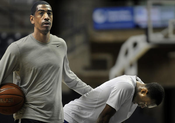 UConn assistant coach Kevin Ollie, left, has a pat for Ryan Boatright during a workout Tuesday at Gampel Pavilion.