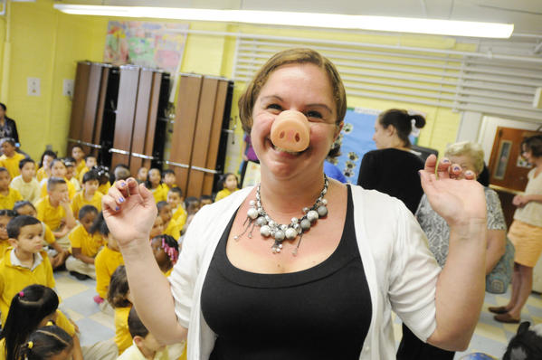 Dean of students Marcie Morrocco of the Asian Studies Academy in Hartford wears a pig snout after she and princiopal Stacey McCann  challenged the school¿s 223 students to read for at least 40 additional minutes a day as part of their ¿Pig Out on Reading¿ initiative. If the students kept their end of the bargain, one school official voted by the students would kiss Daisy.  All 223 students met the challenge and, in a tie vote, elected to have both the principal and the dean of students kiss Daisy, who belongs to Paul Minor of Bristol and who lives on the Minor farm there. The children got to meet and pet Daisy as well as Lily, the Minor family dog.