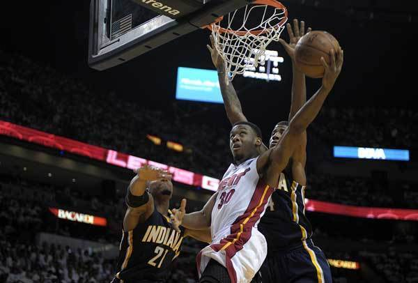 Miami Heat guard Norris Cole takes a shot against Indiana Pacers Paul George and David West during the third quarter of their Round 2, Game 5 playoff game, Tuesday, May 22, 2012, at AmericanAirlines Arena.
