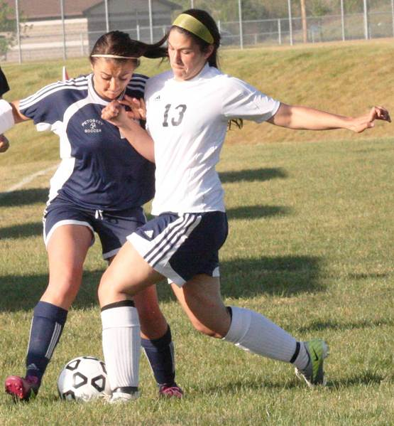 Hayley Fettig (left) of Petoskey battles Natasha Gabara of Cadillac for the ball Tuesday during a 4-1 Northmen win at Cadillac. The Northmen can wrap up their fourth consecutive Big North Conference championship on Thursday with a win at home against Traverse City Central.