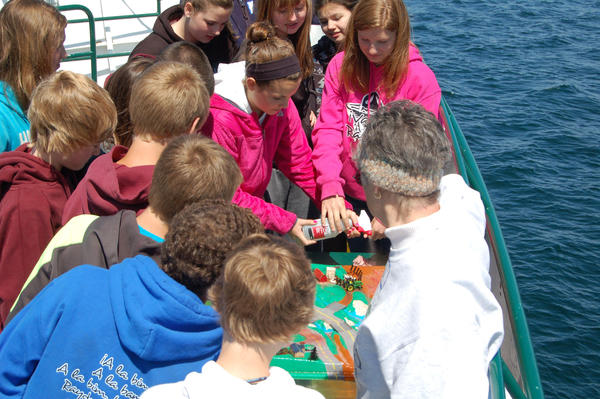 Volunteer Diane Strzelinski shows Charlevoix Middle School students how pollutants work their way into freshwater systems during a recent outing on the Beaver Islander boat on Lake Charlevoix.