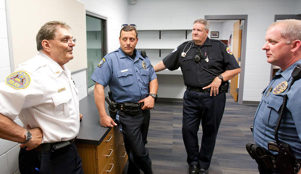 Freemansburg's Police Chief George Bruneio (left) talks with Bethlehem Township policemen Robert Stametz (left center), Brian Frante (right) and his son Robert Bruneio (right center), a Lehigh University Policeman and Freemansburg Firefighter at Freemansburg's new Police Building Dedication on Tuesday afternoon. The building was dedicated as the Robert A Lasso Police Center after slain officer Lasso. George Hitcho Jr. was found guilty of first degree murder last week in the shooting of Officer Lasso last August 11th, 2011 as he responded to a dispute Hitcho had with a neighbor.