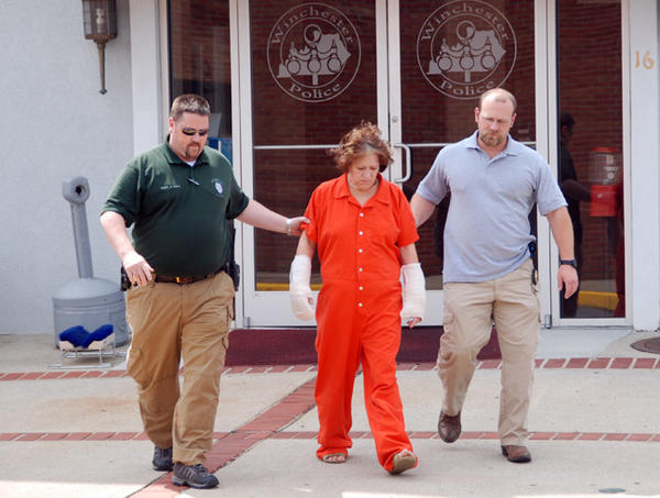 Murder suspect Lillie Stanton, center, walks to jail Wednesday afternoon following her release from the hospital, escorted by Winchester Police Capt. James Hall, left, and Sgt. Tom Beall. She is charged with killing her daughter and infant granddaughter Sunday.