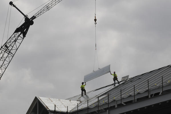 A sheet metal roof section is lowered down to construction workers at a new  building being built on the Central Connecticut State University campus Wednesday afternoon.  Construction of the projected $38 million classroom building started last August. The 75,000 square foot  building is scheduled to open in mid-2013 and will house classes and faculty offices for the sociology, history, anthropology, geography and political science departments, university officials said. It will have 17 classrooms, five seminar rooms, seven labs and 71 offices for faculty and administrators