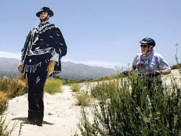 "Ernie Hess of Montrose looks at a cut out of Clint Eastwood placed on a ridge at the top of the Verdugo Hills overlooking the Glendale (2) Freeway. A note taped to the back of the cutout says ""The World Sees Art and the Art Watches Back"" Glendale Public Art Project."