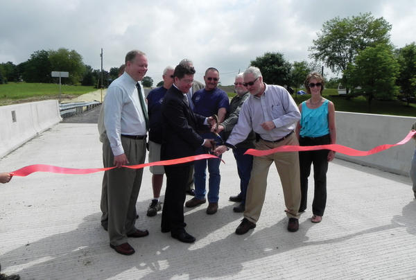 Franklin County Commissioners, from left, Bob Ziobrowski, David Keller and Robert Thomas cut a ribbon for one of the new bridges officially opened near Twin Bridge Meadow Family Campgrounds west of Chambersburg. Joining them are officials from St. Thomas and Hamilton townships and the firms who worked on the project.