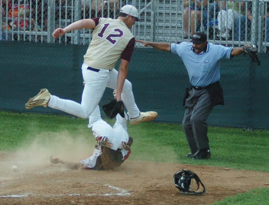 Clark base runner Malik Warner slides safely into home plate following a passed ball underneath flying Bourbon¿County pitcher Chase Mullins in the second inning of the Cardinals¿ 5-3 triumph over the Colonels Wednesday night.