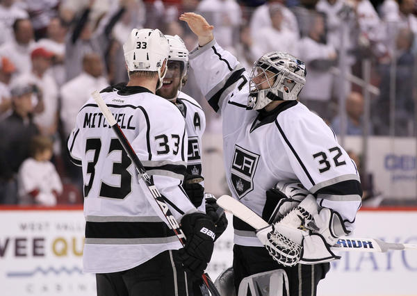Willie Mitchell (left), Anze Kopitar and goaltender Jonathan Quick of the Los Angeles Kings celebrate a 4-3 overtime victory against the Phoenix Coyotes in Game 5 of the Western Conference final Tuesday.
