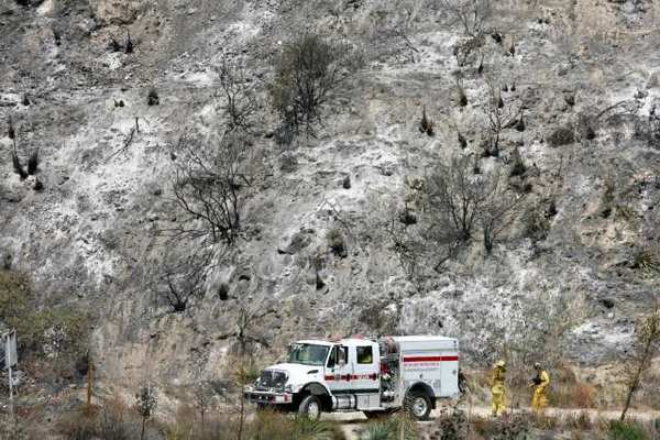 Fire crews work in a barren landscape in Angeles National Forest after the brush fire passed through on Aug. 28, 2009.