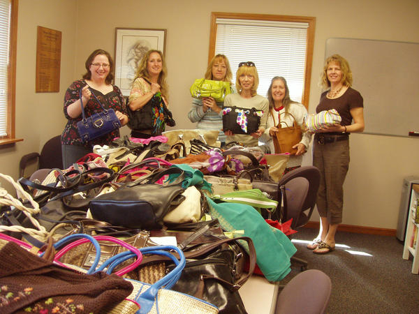 The Women's Resource Center of Northern Michigan receives a large donation of fully stocked purses from the southern Michigan nonprofit Handbags of Hope to benefit survivors of domestic abuse and sexual assault. Accepting the donation are Women's Resource Center staff Danielle Ross, Leslie Turovaara, Lisa Devergilio and Jackie Bobcean of Handbags of Hope, Sue Bissell and Gail Kloss.