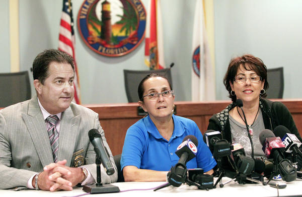 Village of Key Biscayne Police Officer Nelia Real, center, speaks during a press conference Thursday May 24, 2012 about being shot in her face and neck two weeks earlier during her commute home on Florida's Turnpike. At left is Village of Key Biscayne Police Department Chief Charles R. Press, who held the conference. Real's partner, Yolanda Dearmas, is at right. Village Mayor Franklin Caplan also attended.